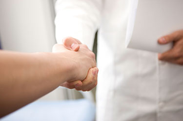 Arzt drückt Patientin die Hand